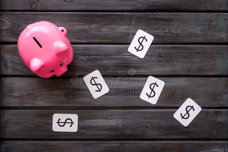 Moneybox en la forma de la muestra del cerdo y de dólar en la opinión superior del fondo de madera imágenes de archivo libres de regalías