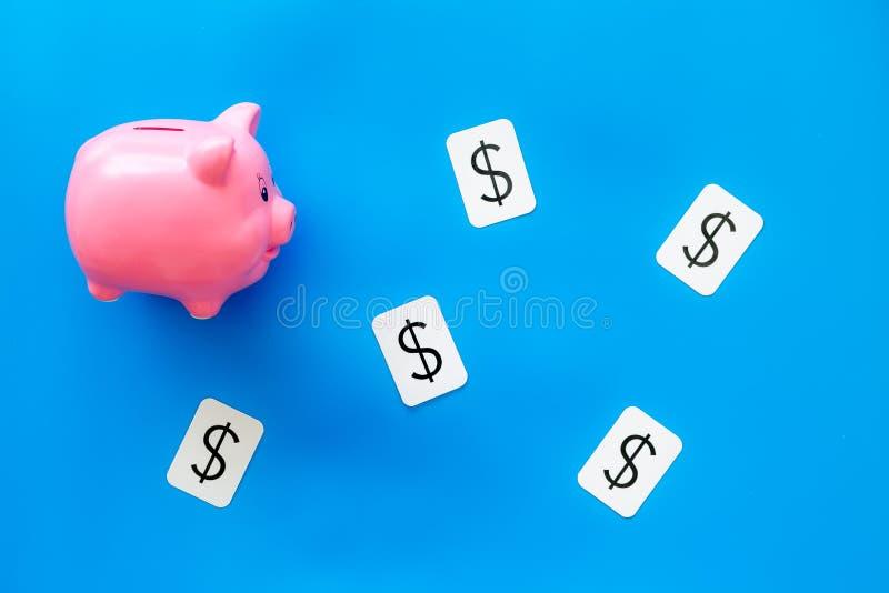 Moneybox en la forma de la muestra del cerdo y de dólar para el presupuesto de negocio en la opinión superior del fondo azul imagen de archivo libre de regalías