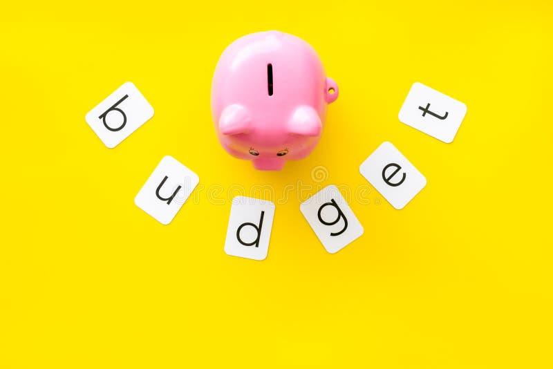 Moneybox en la forma del cerdo, presupuesto de la palabra en maqueta amarilla de la opinión superior del fondo foto de archivo libre de regalías