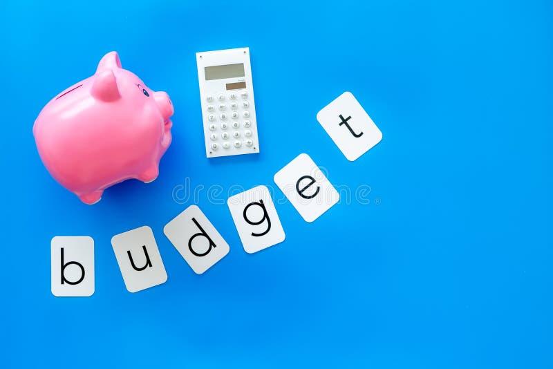 Moneybox en la forma del cerdo, del presupuesto de la palabra y de la calculadora en maqueta azul de la opinión superior del fond imágenes de archivo libres de regalías