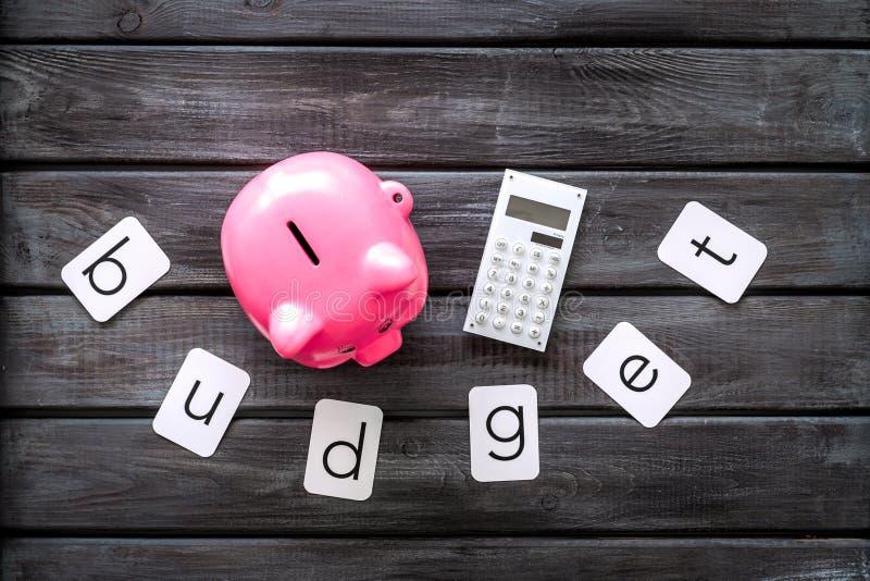 Moneybox en la forma del cerdo, del presupuesto de la palabra y de la calculadora en la opinión superior del fondo de madera foto de archivo libre de regalías