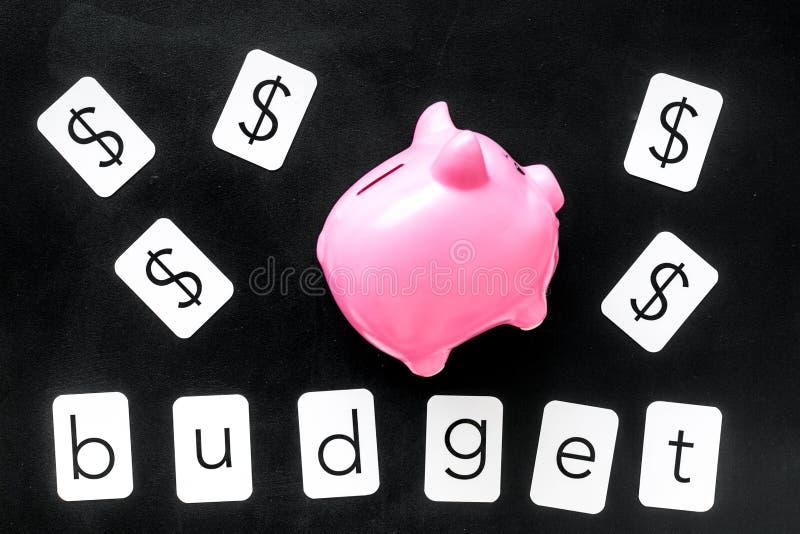 Moneybox en la forma del cerdo, del presupuesto de la palabra y de la muestra de dólar en la opinión superior del fondo negro fotografía de archivo libre de regalías