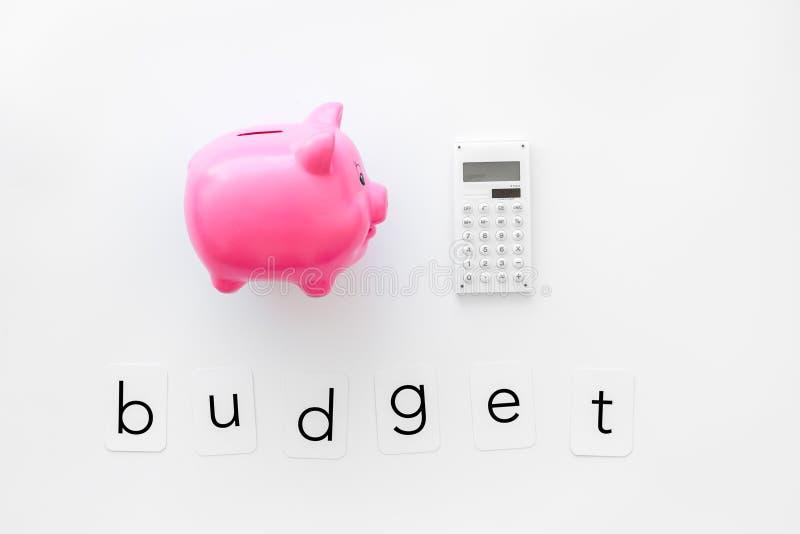 Moneybox en la forma del cerdo y de la calculadora para el presupuesto de negocio en la opinión superior del fondo blanco foto de archivo libre de regalías