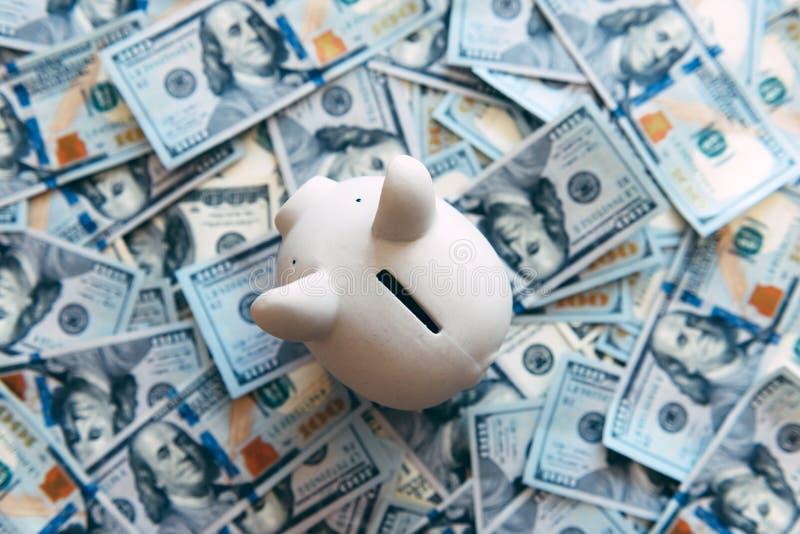 Moneybox leitão com dinheiro do dólar fotografia de stock