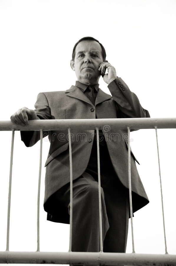 Moneymaker. Wise middle aged boss on the phone royalty free stock image