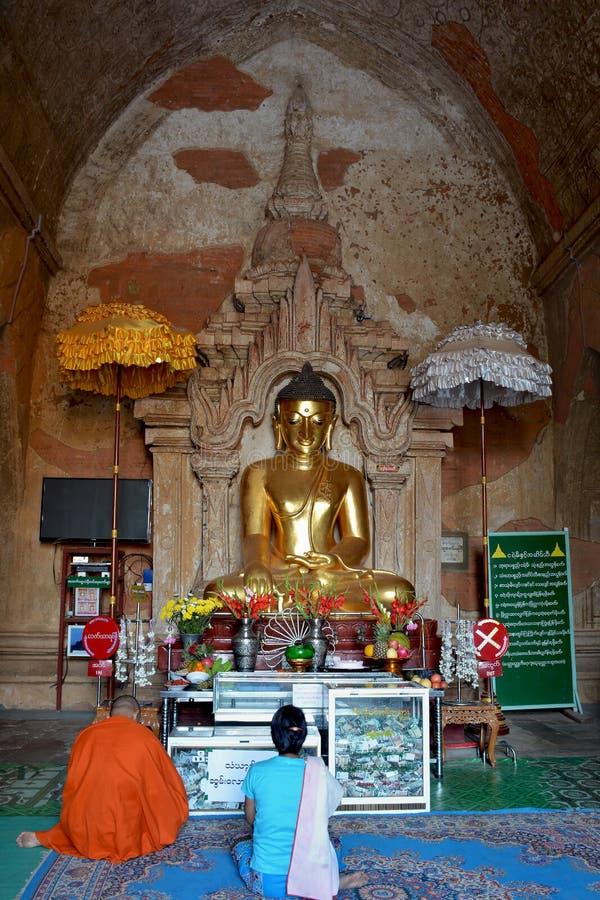 Monge budista e mulher de myanmar que reza ao st dourado de Lord Buddha imagem de stock