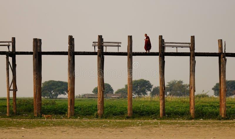 Monge burmese na roupa vermelha que anda na ponte de Ubein imagens de stock royalty free