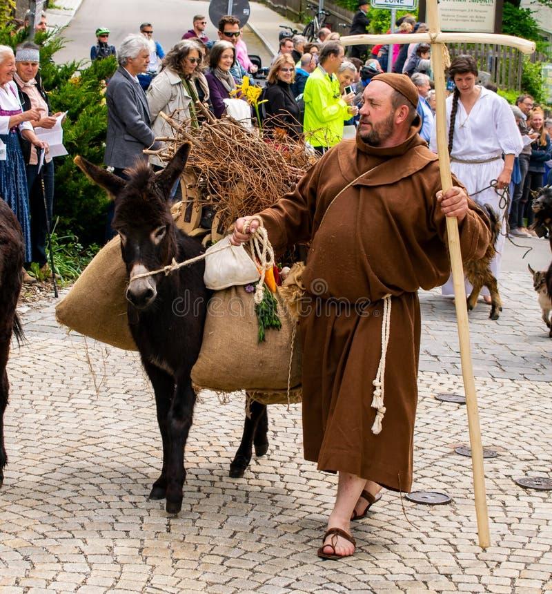 A monge corre com seu asno durante uma procissão em Garmisch-Partenkirchen, Garmisch-Partenkirchen, Alemanha - 20 de maio imagem de stock royalty free