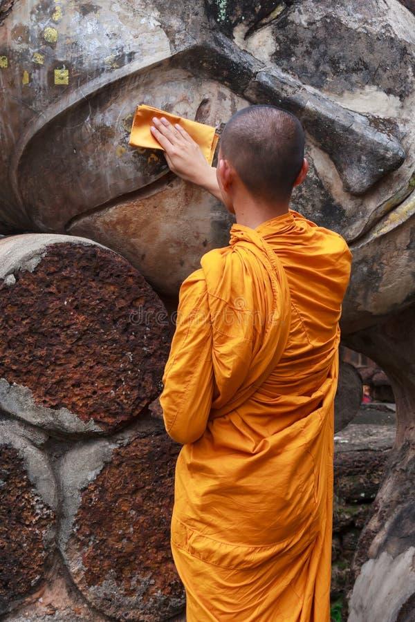 A monge está limpando a estátua da Buda foto de stock royalty free
