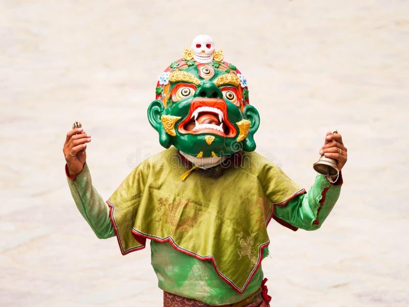 A monge não identificada com sino ritual e vajra executa uma dança mascarada e trajada religiosa do mistério do budismo tibetano  imagem de stock royalty free