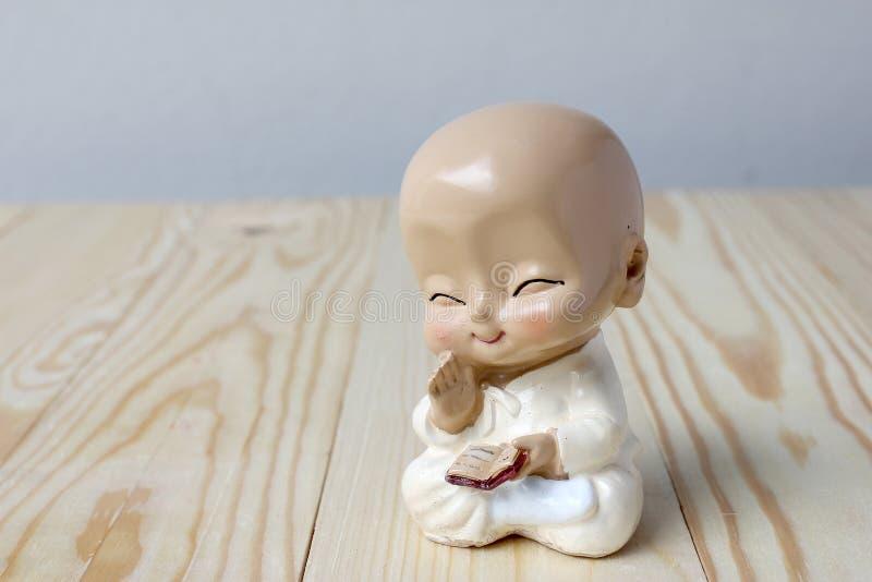Monge pequena que reza, neófito da estátua no fundo da madeira de pinho imagens de stock royalty free