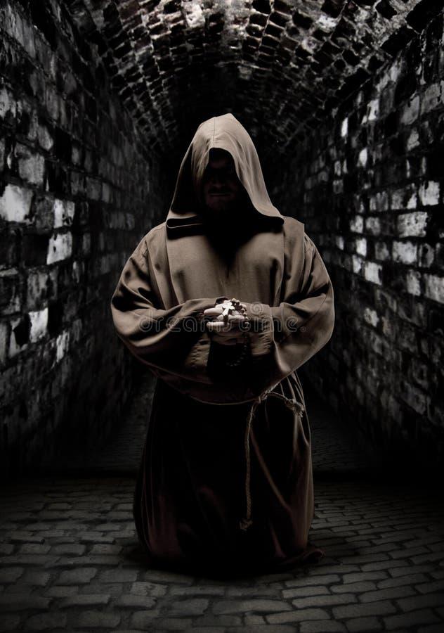 Monge Praying no corredor escuro do templo fotografia de stock royalty free
