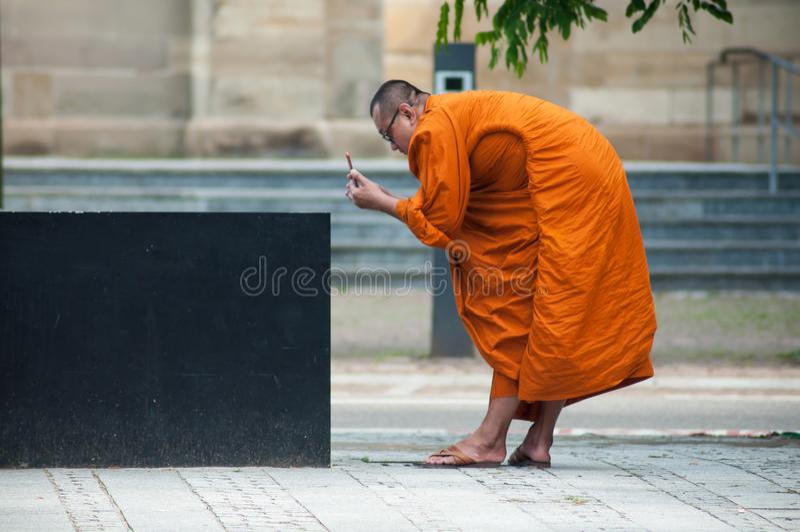 monge tibetana que toma uma imagem da fonte em um lugar fotografia de stock