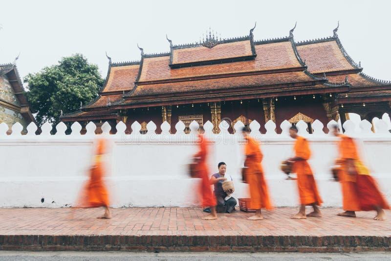 Monges budistas durante a esmola sagrado tradicional Laotian que dá a cerimônia na cidade de Luang Prabang, Laos fotografia de stock