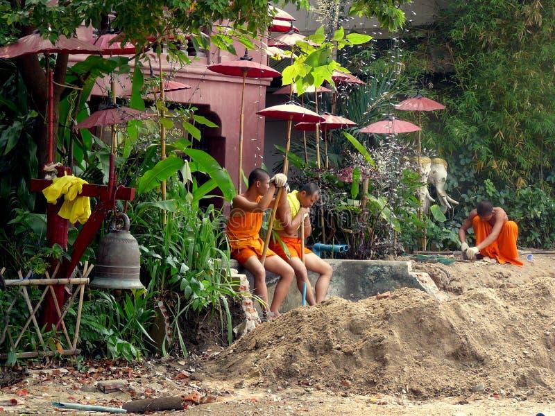 Monges budistas novas que trabalham em um Wat foto de stock