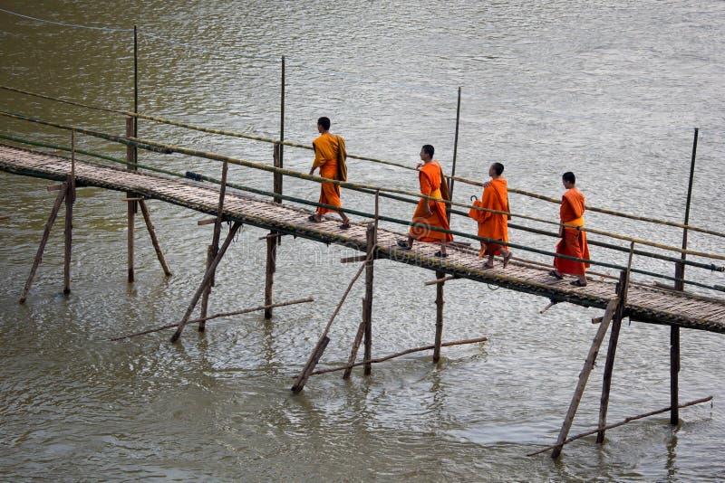 Monges budistas que cruzam a ponte de bambu em Luang Prabang, Laos imagem de stock