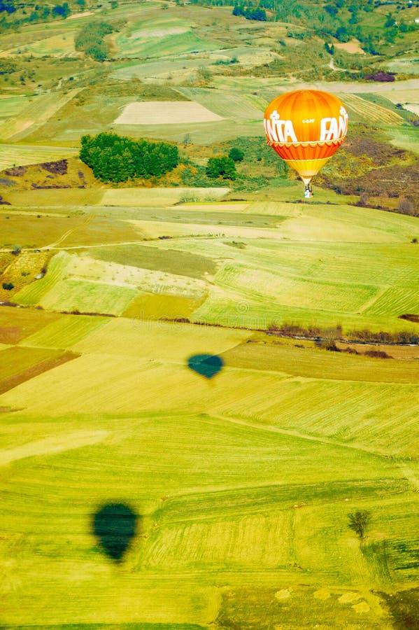 Mongolfiera arancio sopra i campi coltivati, concorrenza di sport fotografia stock libera da diritti