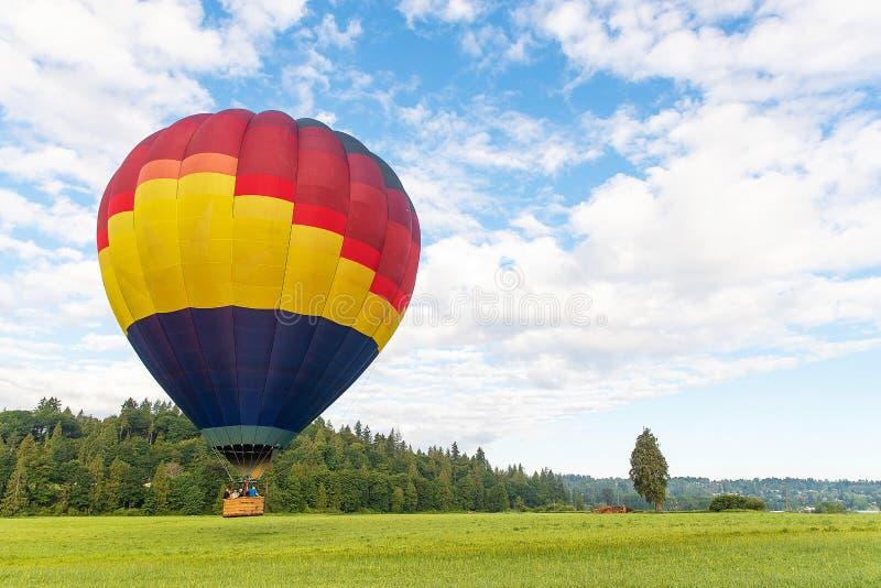 Mongolfiera variopinta che galleggia sotto il cielo blu fotografia stock