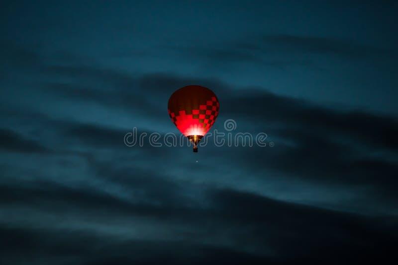 Mongolfiera variopinta nel rosa scuro e nei colori porpora che emettono luce in un cielo blu scuro di primo mattino con le nuvole fotografia stock