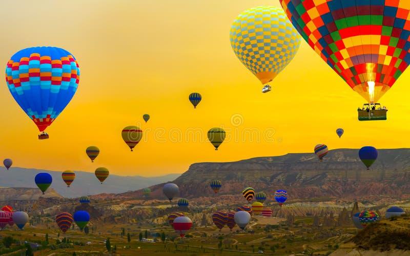 Mongolfiere di tramonto che atterrano in una montagna Cappadocia Goreme immagini stock
