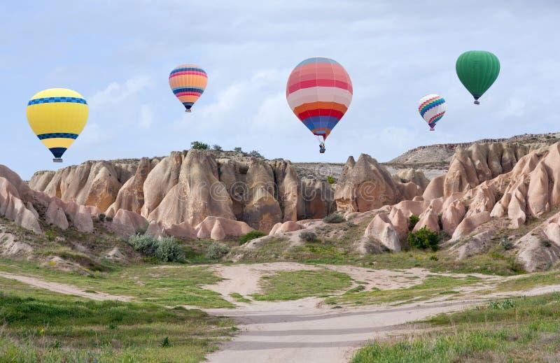 Mongolfiere variopinte che sorvolano Cappadocia, Turchia immagini stock libere da diritti