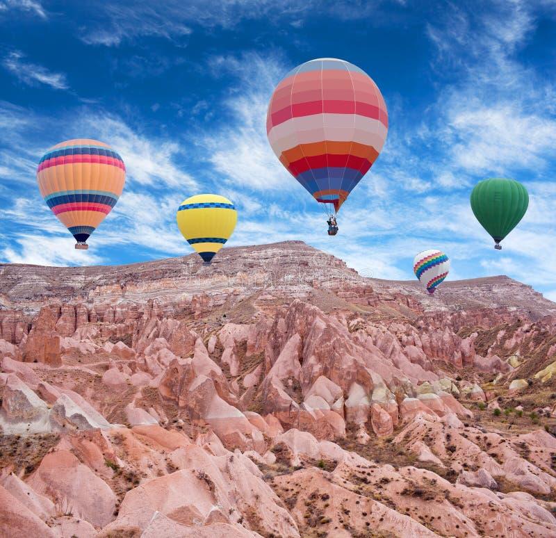Mongolfiere variopinte che sorvolano valle rossa in Cappadocia, fotografie stock libere da diritti