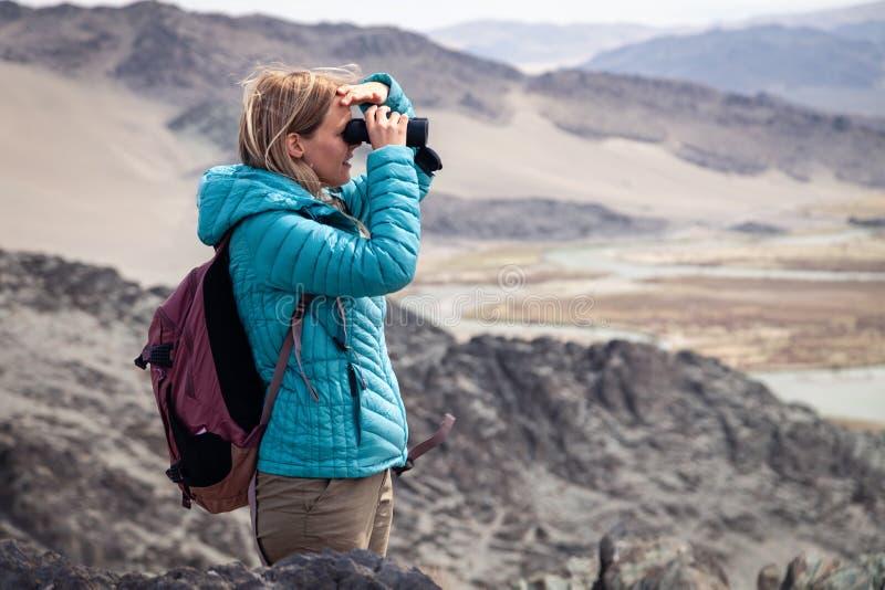 Mongolia Ulgii 2019-05-04 European beautiful girl in blue jacket looking through binocular into the distance, eagle. Watching, hiking, climbing, walking stock photos
