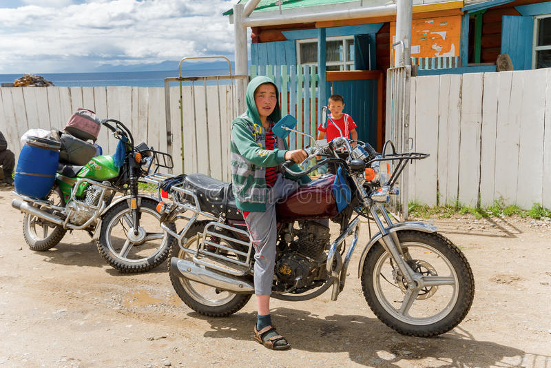 Mongolian boy on a motorcycle stock images