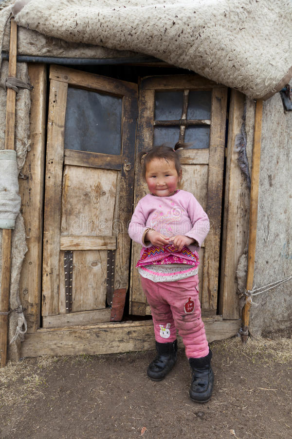 Mongolian child infront of Ger. Portrait of Mongolian child infront of Ger entrance wearing pink royalty free stock photography