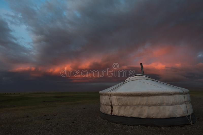Mongolian ger under dramatic evening skies. A ger in central Mongolia sits under dramatic and moody evening stormy skies at sunset stock image