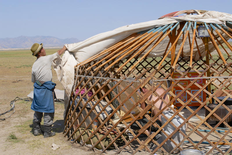 Mongolian men assemble yurt in steppe, circa Harhorin, Mongolia. CIRCA HARHORIN, MONGOLIA - AUGUST 25, 2006: Unidentified Mongolian men assemble yurt (ger or royalty free stock images