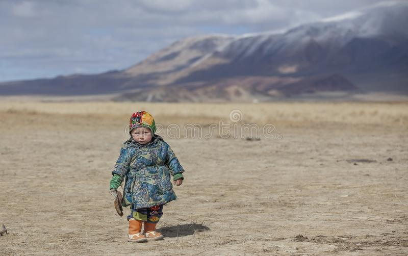Mongolian nomad boy in traditional deel - overcoat worn by people of Mongolia royalty free stock photo