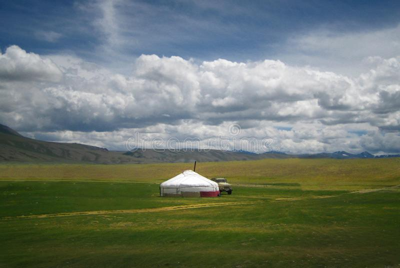 Mongolian yurt, called ger, in a landscape of north-west Mongolia. Mongolian yurt, called ger in a landscape of nort-west mongolia. Clouds over the green stock images