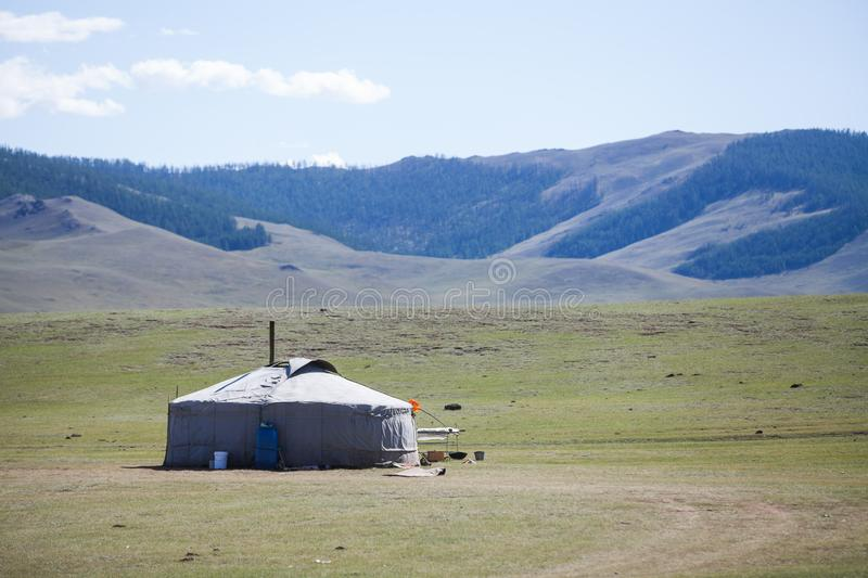 Mongolian yurt on a hill. Color image of a Mongolian yurt on a green field stock photo