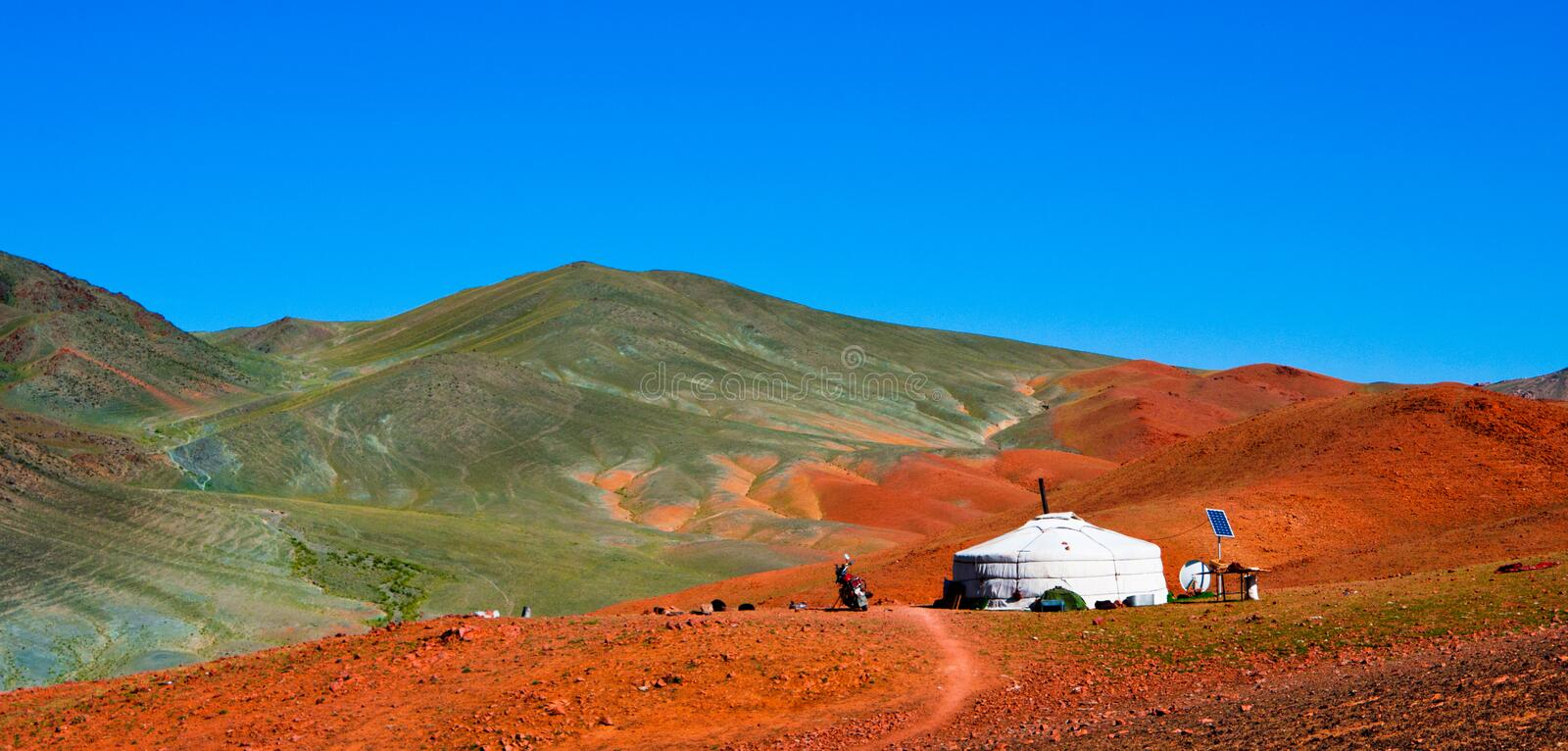 Mongolian yurt in the mountains. Traditional mongolian yurt (ger) in the Mongolian Altai mountains: lifeless soil, red stony ground, blue sky stock photography
