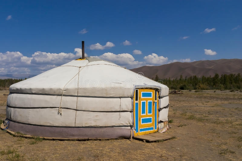 A mongolian yurt in the steppe. Beautiful clouds with the blue sky on the background royalty free stock images