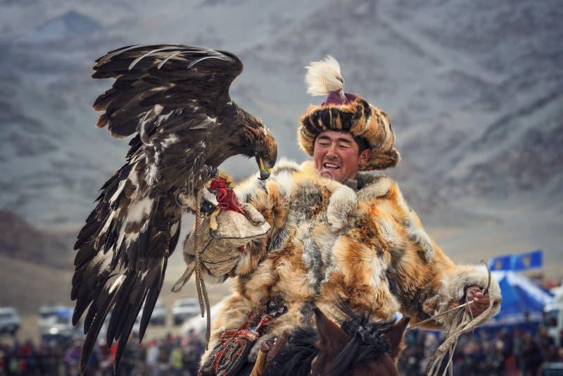 Mongoliet Traditionella guld- Eagle Festival Okända mongoliska Hunter Berkutchi On Horse With guld- Eagle Falkenerarkonst i västr arkivfoton
