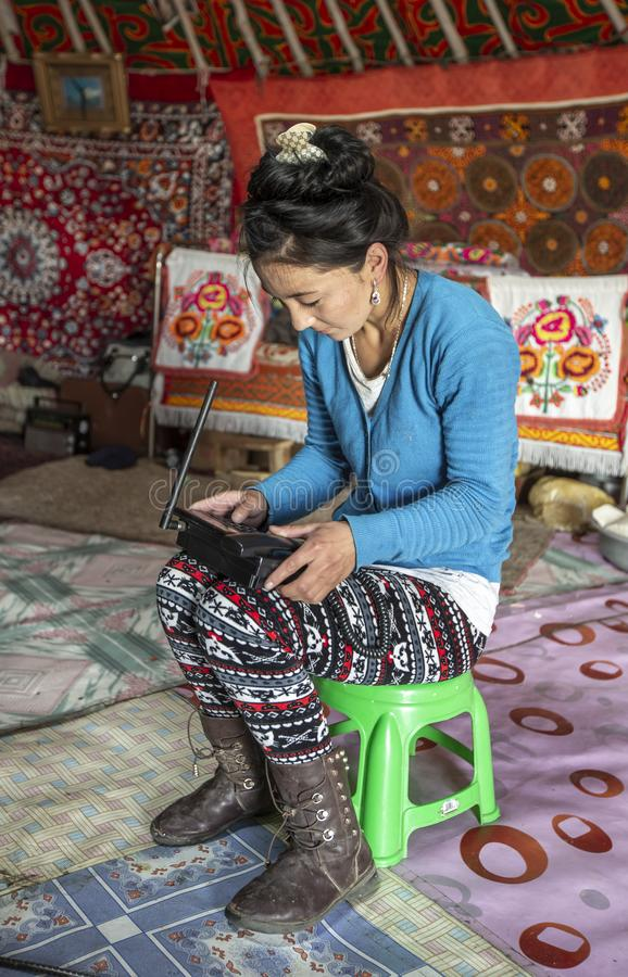 Mongolische Nomadefrau in ihrem Haupt-yurt, auf einen Telefonanruf wartend stockbild