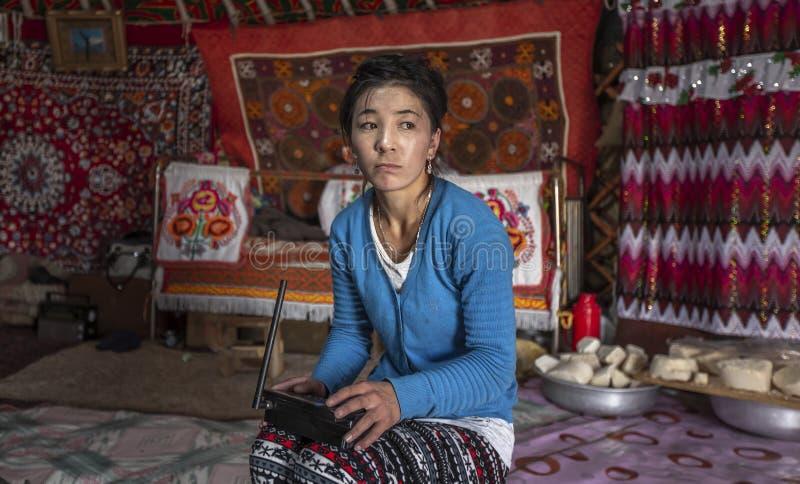 Mongolische Nomadefrau in ihrem Haupt-yurt, auf einen Telefonanruf wartend stockfotos