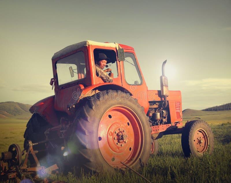 Mongolisches Konzept Landwirt-Driving Tractor Fields Agicultural lizenzfreie stockbilder