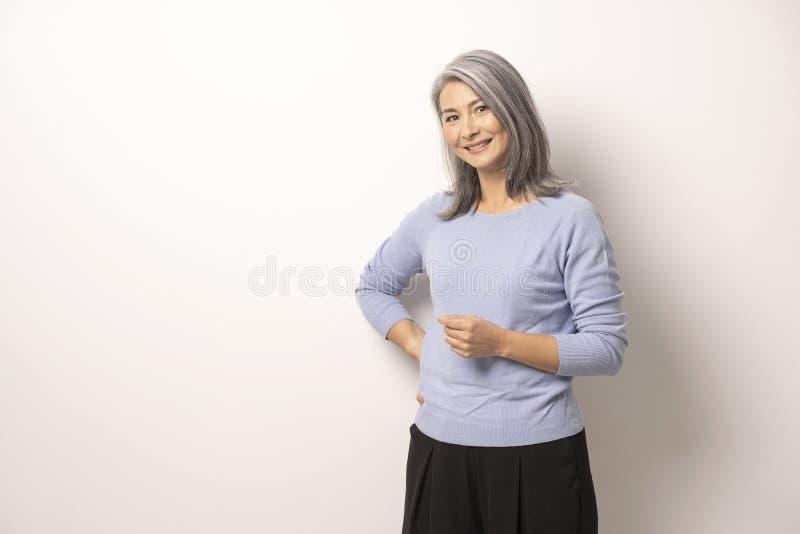 Mongoliska härliga Gray Haired Woman på en vit bakgrund arkivbild