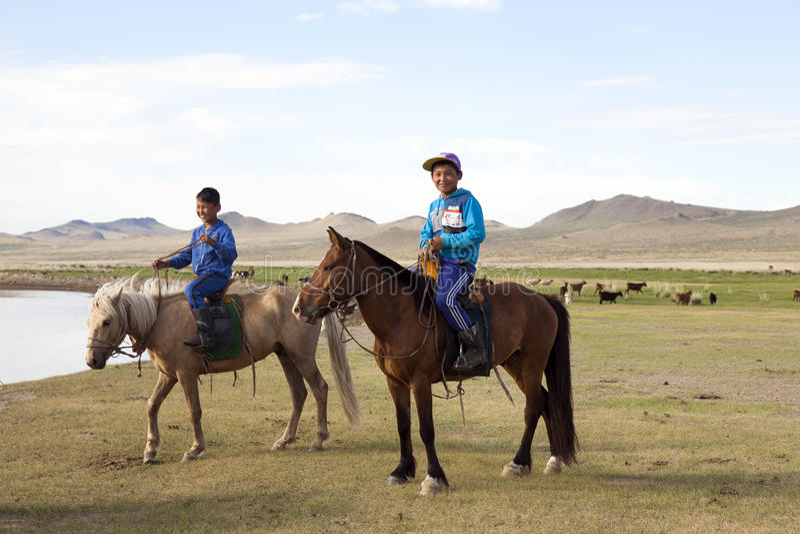Mongoliska pojkar på hästrygg royaltyfri fotografi