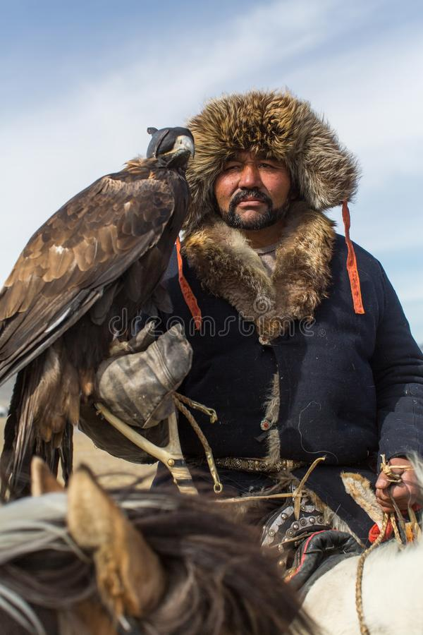 Mongolskiego kazach Eagle myśliwego tradycyjna odzież, mienie złoty orzeł na jego ręce w pustynnej górze Zachodni Mongolia zdjęcia royalty free