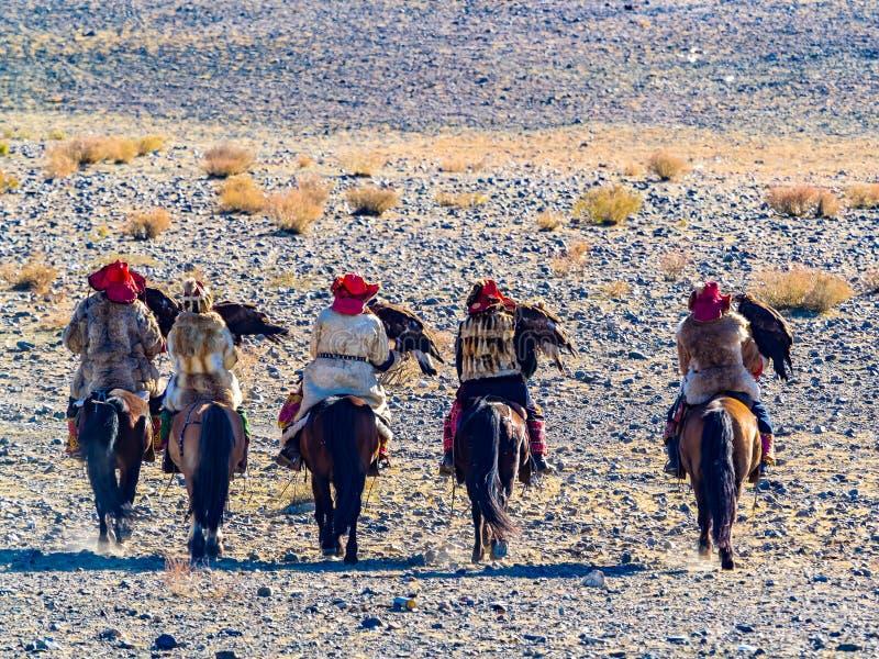 Mongools Gouden Eagle Hunter in traditionele kleding die op horseback aan de Gouden Eagle Hunter Festival-de concurrentieplaats b stock afbeelding