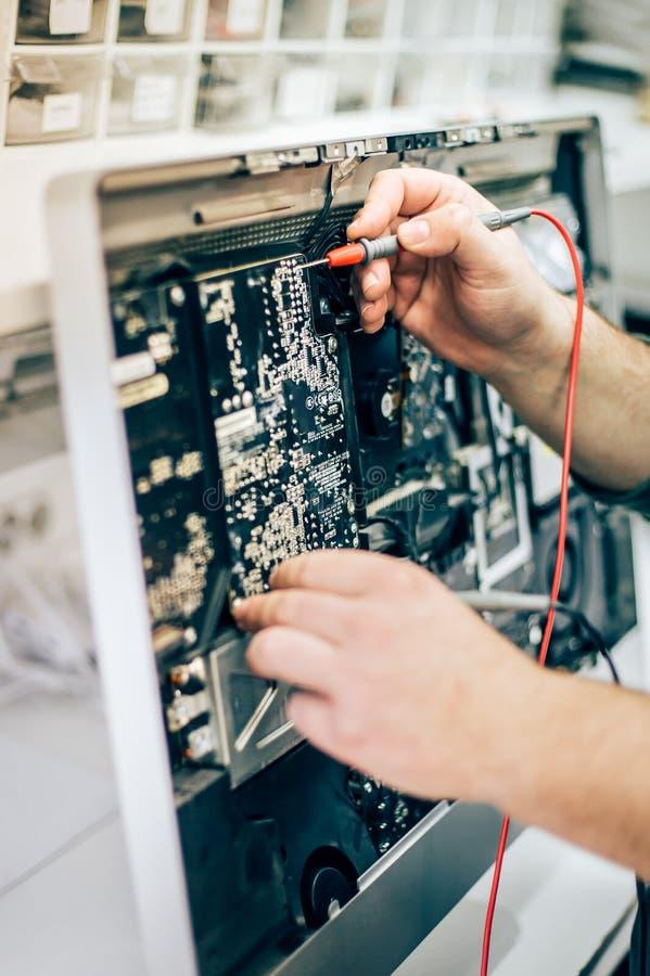 Moniteur défectueux d'ordinateur de réparation de technicien d'ingénieur d'électricien dans le service électrique photographie stock libre de droits