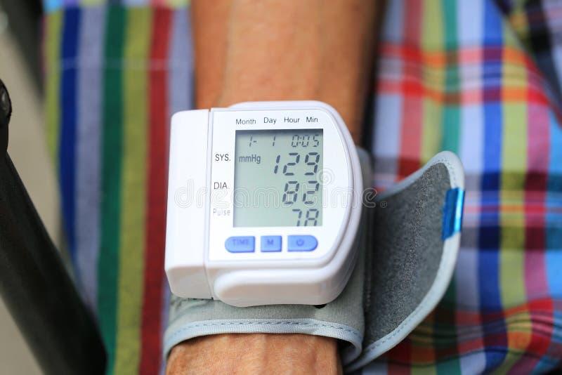 Moniteur de tension artérielle de contrôle d'homme supérieur, concept de soins de santé photographie stock libre de droits