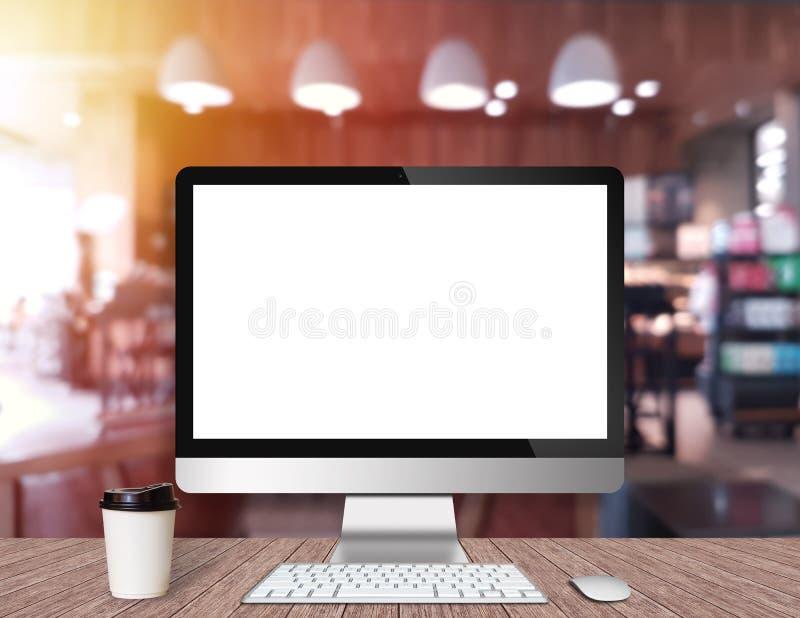 Moniteur moderne d'ordinateur sur un bureau en bois avec le café image libre de droits