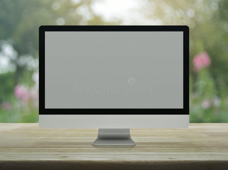 Moniteur moderne de bureau d'ordinateur avec l'écran gris sur la table en bois au-dessus de la fleur et de l'arbre roses de tache image stock