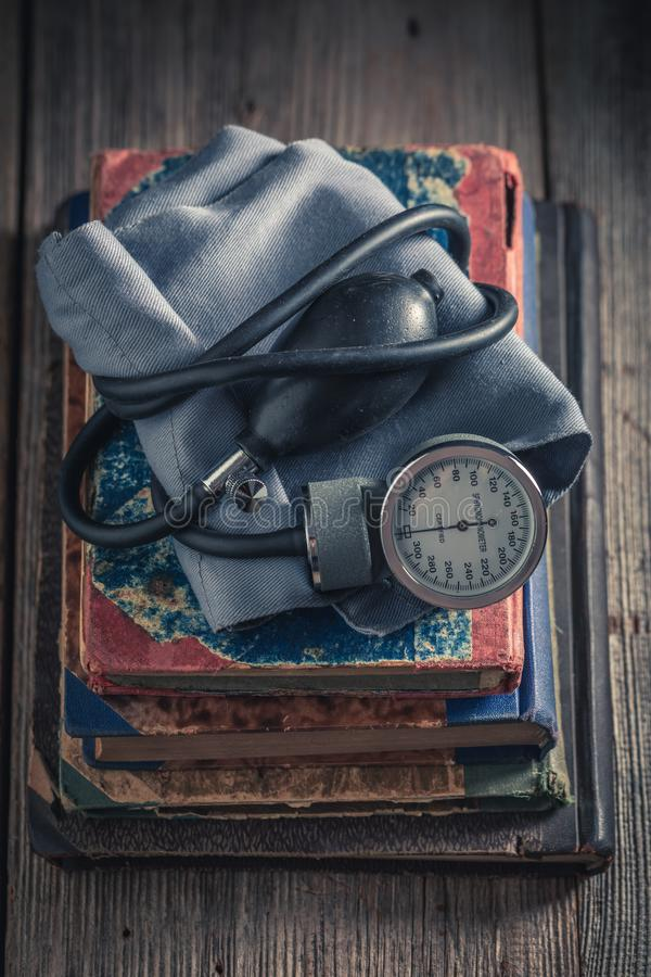 Monitor clássico da pressão sanguínea na pilha de livros velhos fotografia de stock