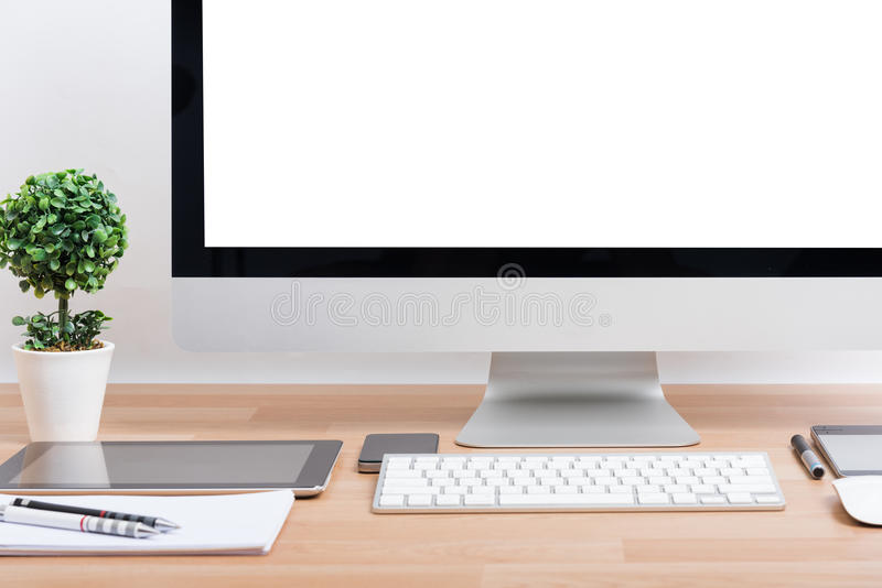 Monitor computer PC, keyboard, Phone. Magic mouse and tablet on wooden desk royalty free stock images